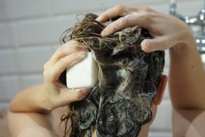Caucasian woman washes her brown hair with shampoo bar or soap, zero waste concept